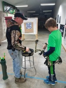 Tim doing an archery instruction with Brody